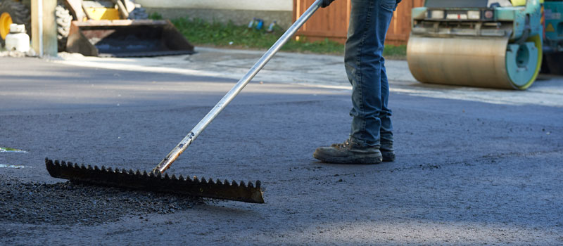 Raking fresh asphalt on a newly paved driveway in Winnipeg