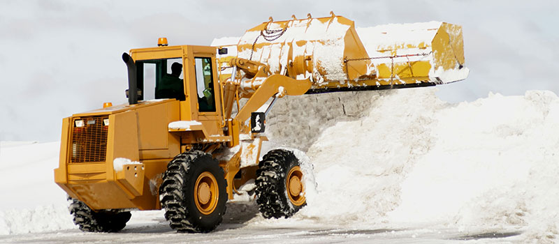 Clearing snow in a commercial parking lot in Winnipeg