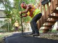 Flattening fresh asphalt on a new walkway installation in Winnipeg